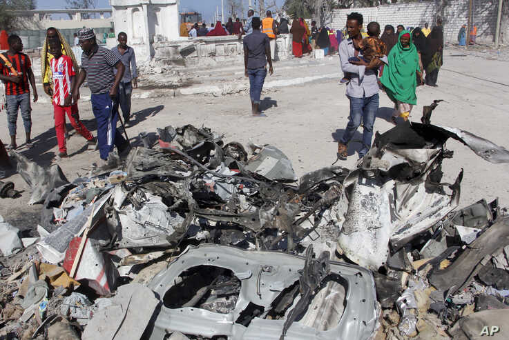 FILE - Somalis walk past debris after a suicide car bomb attack on a government building in the capital Mogadishu, Somalia, Saturday, March 23, 2019. Al-Shabab gunmen stormed the government building after the bomb attack.