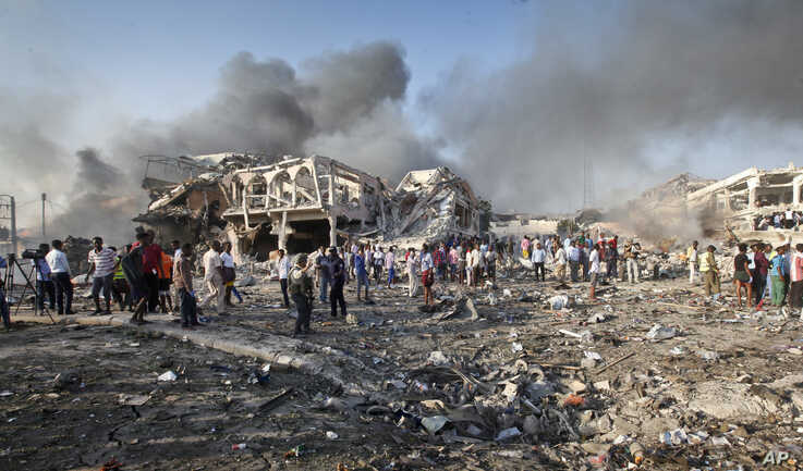 FILE - Somalis gather and search for survivors near destroyed buildings at the scene of a blast in the capital Mogadishu, Somalia, Oct. 14, 2017.