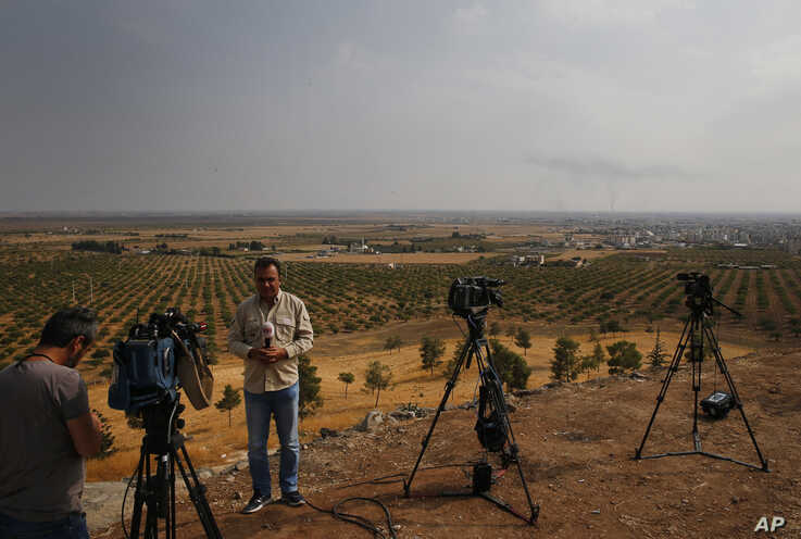 FILE - Journalists work on a hilltop in Ceylanpinar, Sanliurfa province, southeastern Turkey, coverning Ankara's incursion into Syria, Oct. 20, 2019.