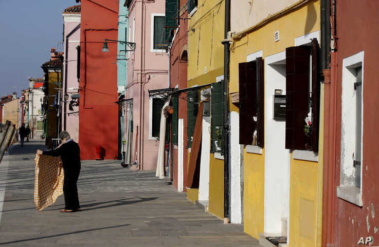 An elderly woman shakes a table cloth outside her house, on Burano island, Italy, Jan. 16, 2020.