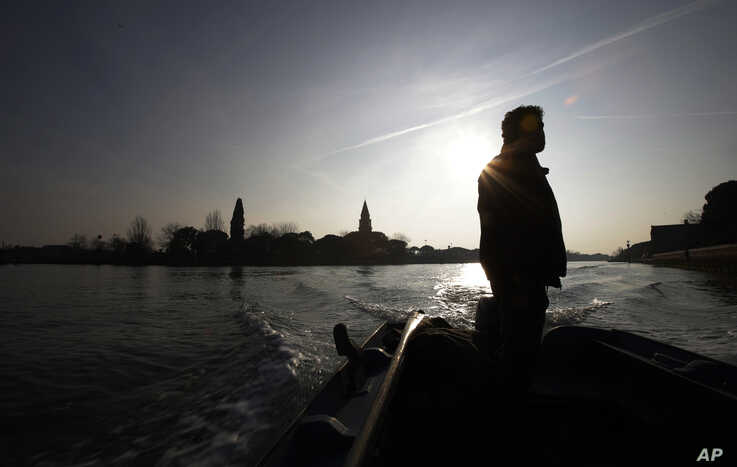 A local fisherman is seen on his boat, near Torcello island, Italy, Jan. 16, 2020.