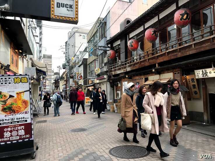 Residents walk down a street in Kyoto, Japan, one of the nations with the most physical assets, like buildings, at risk of clima