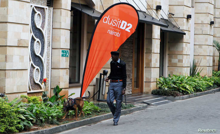 FILE - A security officer and guard dog patrol the DusitD2 Hotel during its reopening after its closure in January of 2019 following an attack by al-Shabab militants, in Nairobi, Kenya, July 31, 2019.