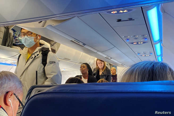 A passenger wearing a mask boards a flight after cases of the coronavirus have been confirmed in the U.S., in Boston, Massachusetts, Jan. 24, 2020.