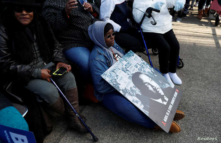 A young woman tries to stay warm as she holds a poster of Martin Luther King Jr. during MLK Day festivities in Columbia, South Carolina, Jan. 20, 2020.
