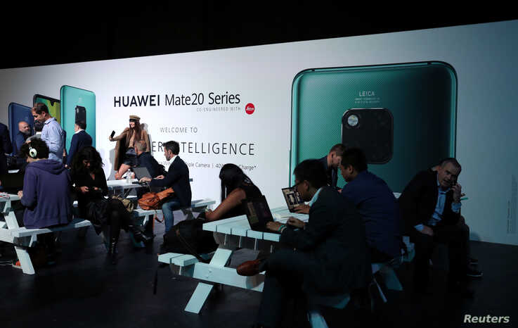 FILE - People attend a Huawei Mate20 smartphone series launch event in London, Britain, Oct. 16, 2018.