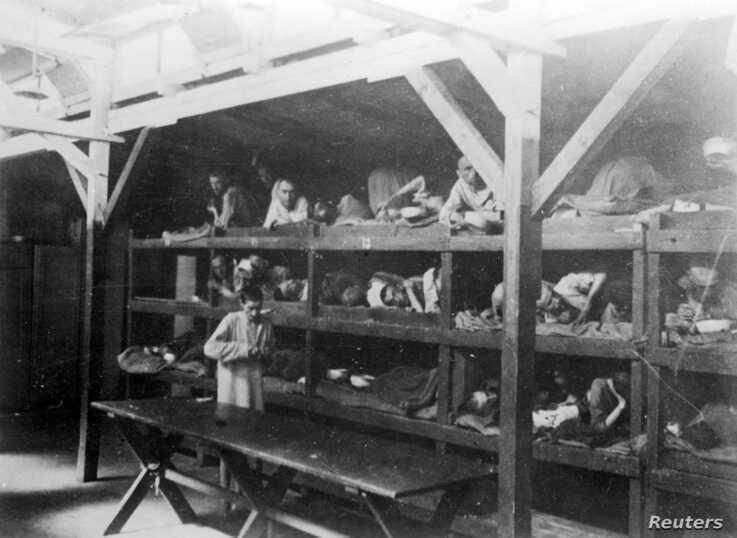 FILE: Inmates are seen lying on bunks in a barrack at Nazi German death camp Auschwitz-Birkenau after its liberation in 1945 in Nazi-occupied Poland, in this undated handout picture obtained by Reuters, Jan. 19, 2020.