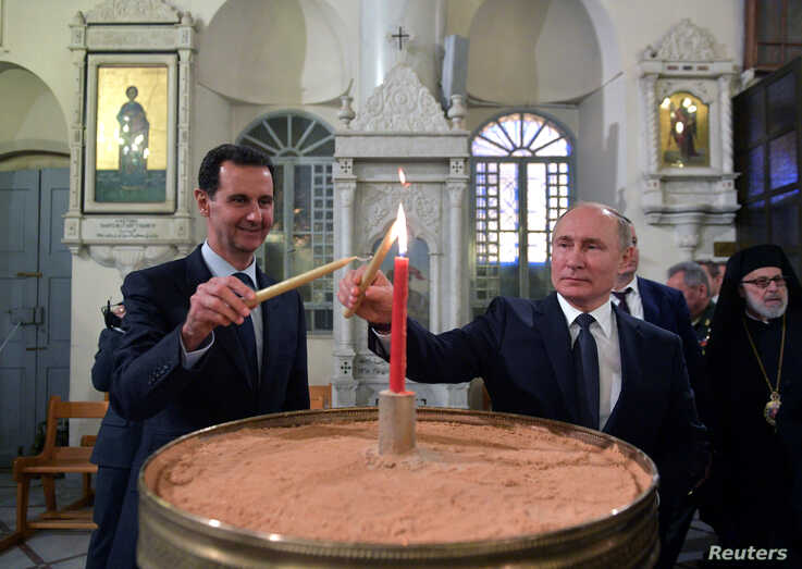 Russian President Vladimir Putin and his Syrian counterpart Bashar al-Assad visit an Orthodox Christian cathedral in Damascus, Syria, Jan. 7, 2020.