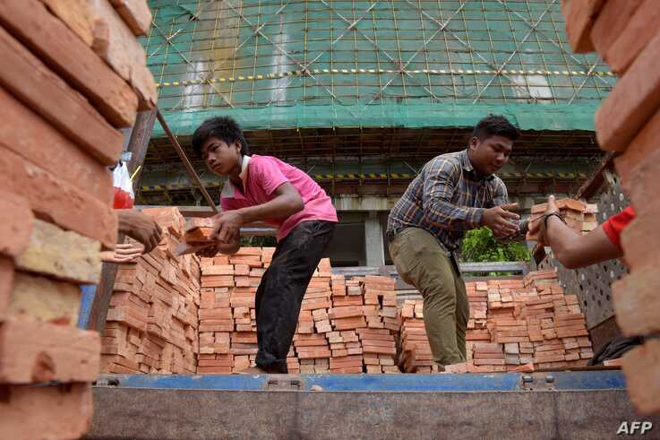 This photograph taken on June 12, 2018 shows Cambodian labourers unloading bricks at an under-construction luxury high-rise…