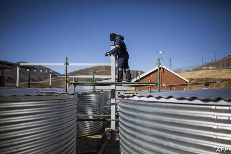 FILE - A worker checks on structures at a facility that grows legal cannabis near Marakabei, Lesotho, Aug. 6, 2019.