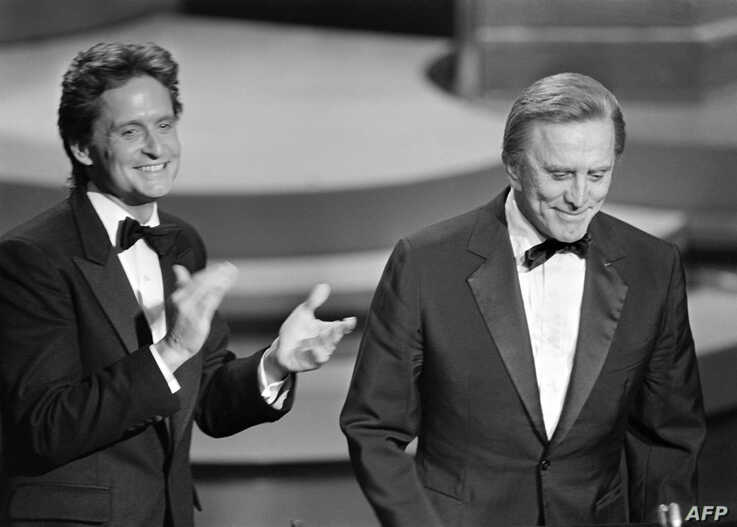 (FILES) In this file photo taken on March 25, 1985 US actor Michael Douglas (L) applauds his father US actor Kirk Douglas…