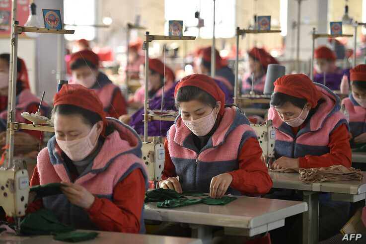 In this photo taken on February 6, 2020, workers of Songyo Knitwear Factory in Pyongyang produce masks for protection against…