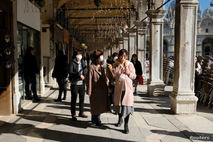 Tourists wearing protective masks walk through Saint Mark's Square in Venice