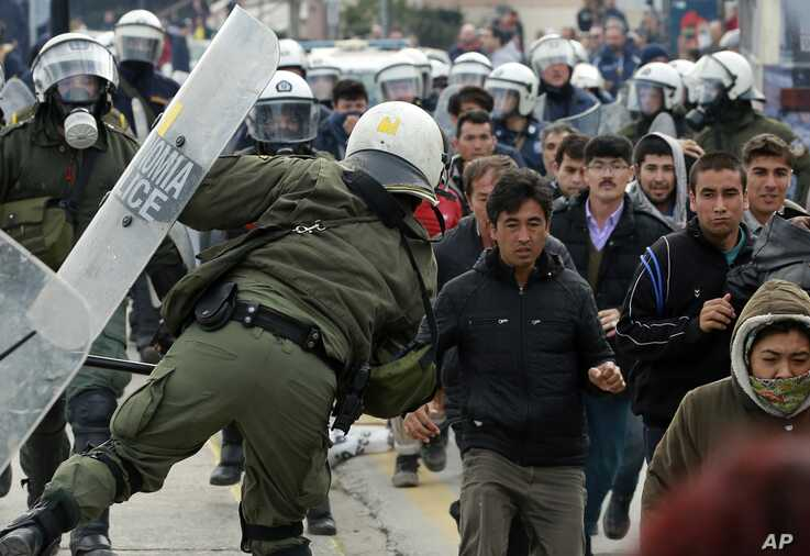 Riot police scuffle with migrants during a protest in Mytilene port on the northeastern Aegean island of Lesbos, Greece, on…