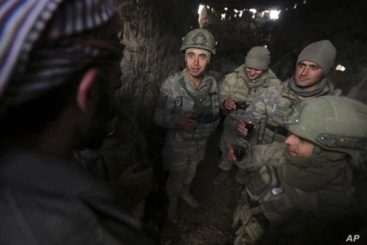 Turkish soldiers drink tea in the Syrian province of Idlib, Monday, Feb. 10, 2020. Turkey said it hit back at Syrian government…