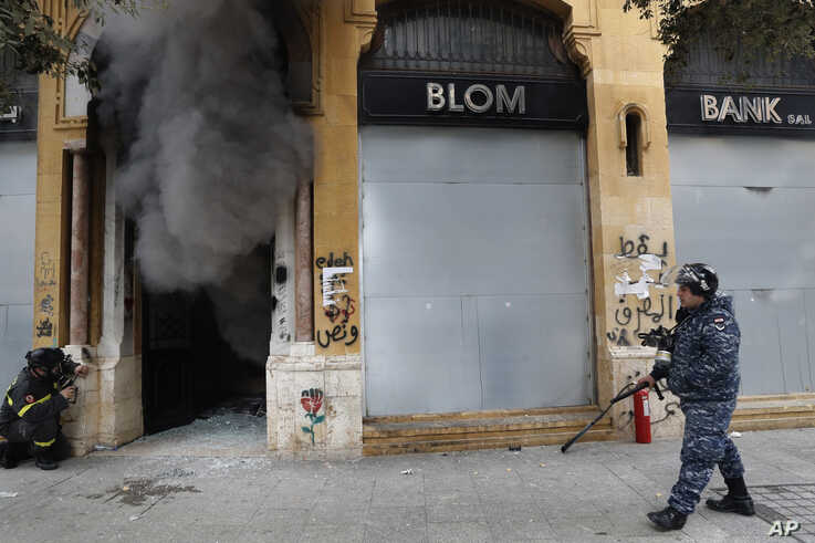 A firefighter looks before entering a bank that was set on fire by anti-government protesters, as a riot policeman passes by,…