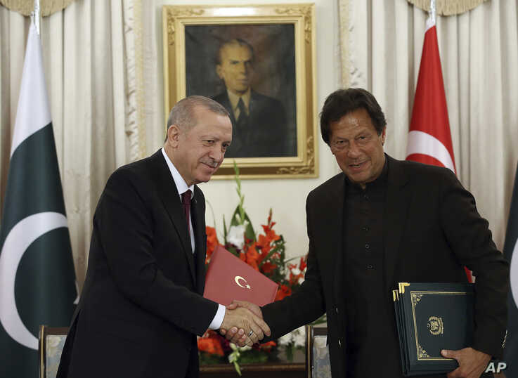 Turkey's President Recep Tayyip Erdogan, left, and Pakistan Prime Minister Imran Khan shake hands after signing of several agreements, in Islamabad, Pakistan, Feb. 14, 2020.