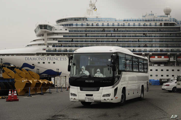 A bus leaves a port where the quarantined Diamond Princess cruise ship is docked, Feb. 15, 2020, in Yokohama, Japan.