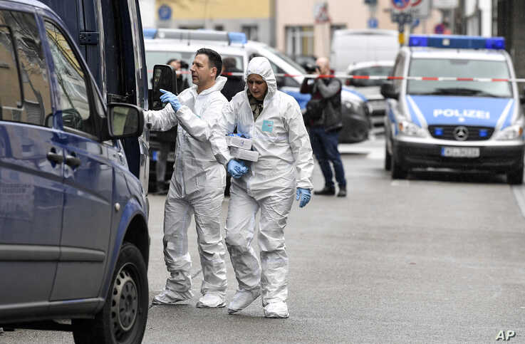 Forensic officers carry baskets from the hookah bar where several people were killed on Wednesday night in Hanau, Germany, Feb. 20, 2020.
