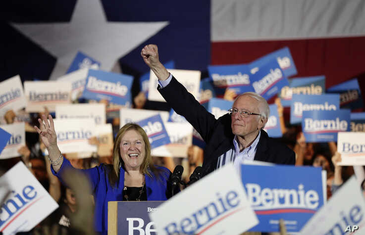 Democratic presidential candidate Sen. Bernie Sanders, I-Vt., right, with his wife Jane, raises his hand as he speaks during a…
