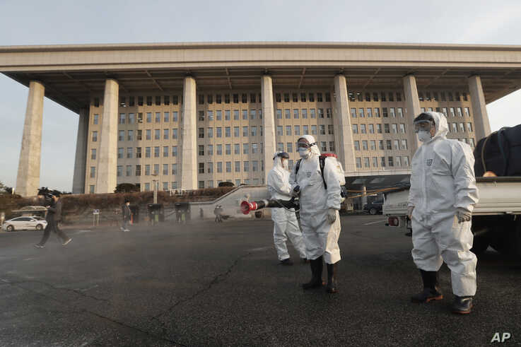 Workers wearing protective suits spray disinfectant as a precaution against the coronavirus at the National Assembly in Seoul,…