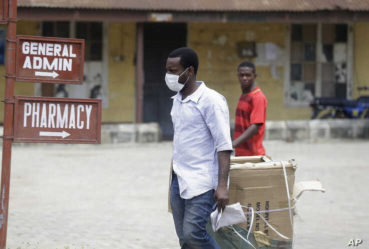 A man wearing face mask walks at the Yaba Mainland hospital where an Italian citizen who entered Nigeria on Tuesday from Milan.