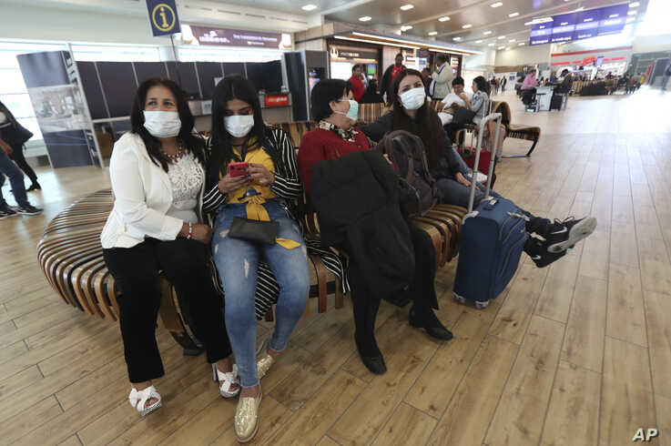 People wearing face masks wearing masks wait for the arrival of their relatives at the Mariscal Sucre International Airport.