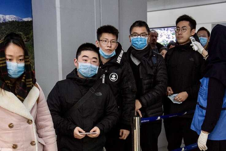 Chinese travelers wearing face masks to protest against the coronavirus undergo a health screening upon arrival at Tehran's Imam Khomeini Airport in this undated photo published by IRNA on Jan. 30, 2020.
