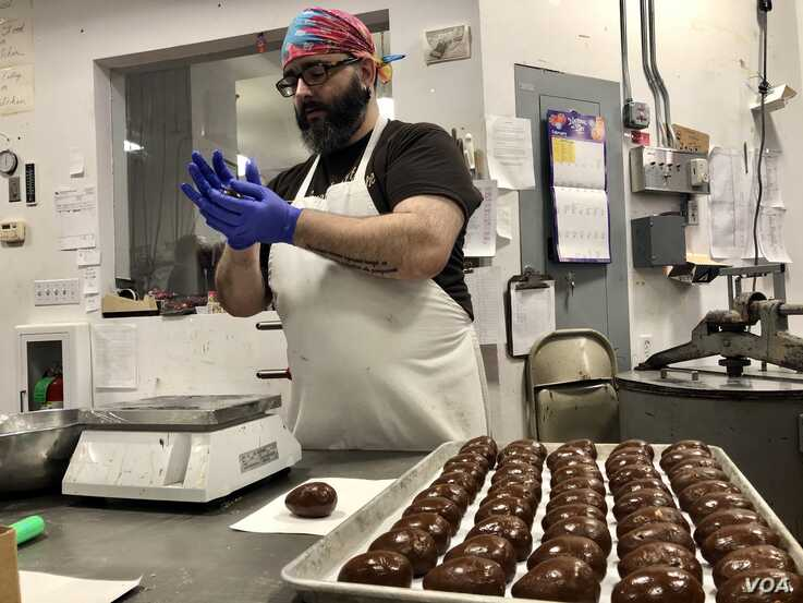 Ed Brand forms chocolate into Easter eggs. The Granite State Candy Shoppe Chocolatier will support South Bend, Indiana Mayor Pete Buttigieg. (VOA/Carolyn Presutti)