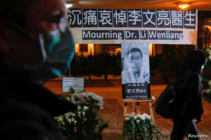 People wearing masks attend a vigil for late Li Wenliang, an ophthalmologist who died of coronavirus at a hospital in Wuhan, in…