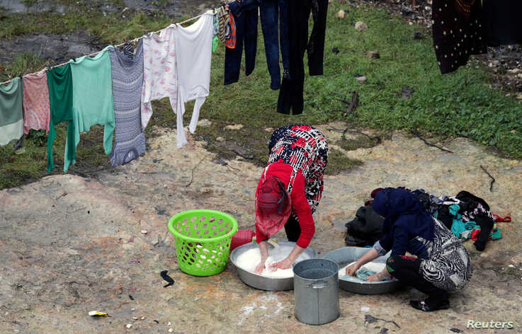 Displaced Syrian women who fled from southern Idlib wash clothes in Afrin, Syria February 7, 2020. REUTERS/Khalil Ashawi -…