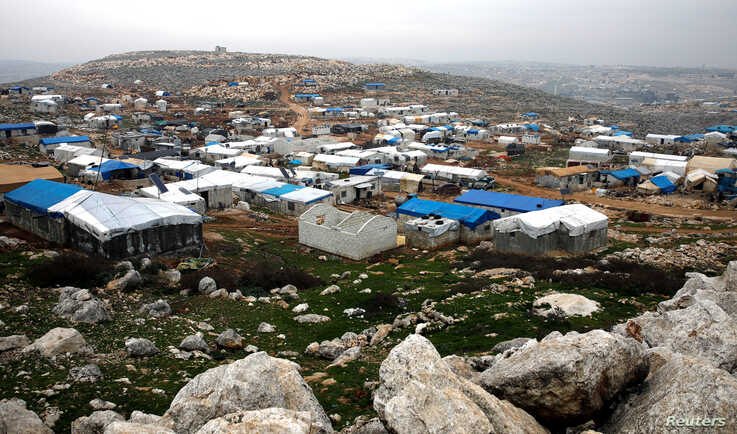 Makeshift shelters of internally displaced Syrians are seen from a hill top as part of an IDP camp located in Sarmada, Idlib…