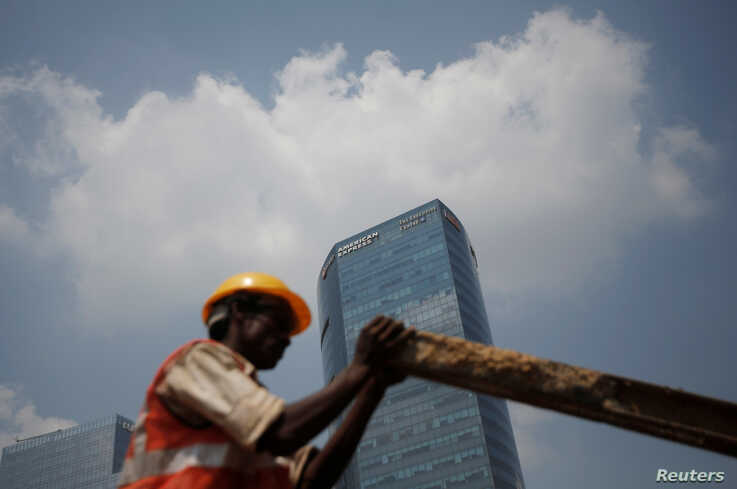 A laborer works at a construction site next to American Express branch in Gurugram on the outskirts of New Delhi, India,…