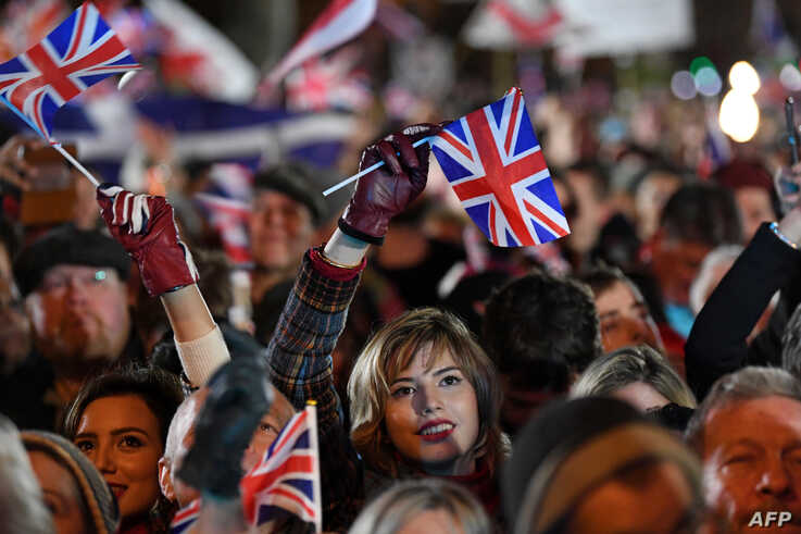 FILE - Brexit supporters wave Union flags during Brexit celebrations in central London, Jan. 31, 2020.