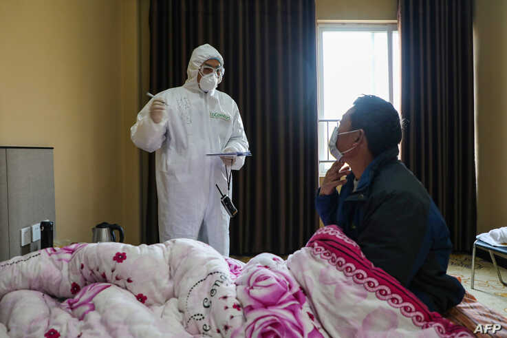 A doctor (L) talks with a patient during his rounds at the ward of a quarantine zone in Wuhan, the epicentre of the new coronavirus outbreak, in China's central Hubei province, Feb. 3, 2020.