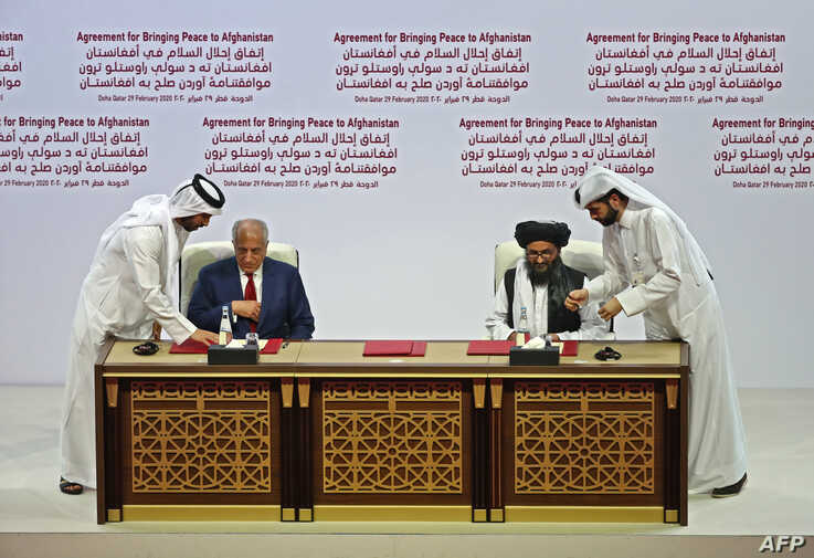 U.S. Special Representative for Afghanistan Reconciliation Zalmay Khalilzad and Taliban deputy chief for political affairs Mullah Abdul Ghani Baradar sign the U.S.-Taliban peace agreement during a ceremony in the Qatari capital Doha, Feb. 29, 2020.