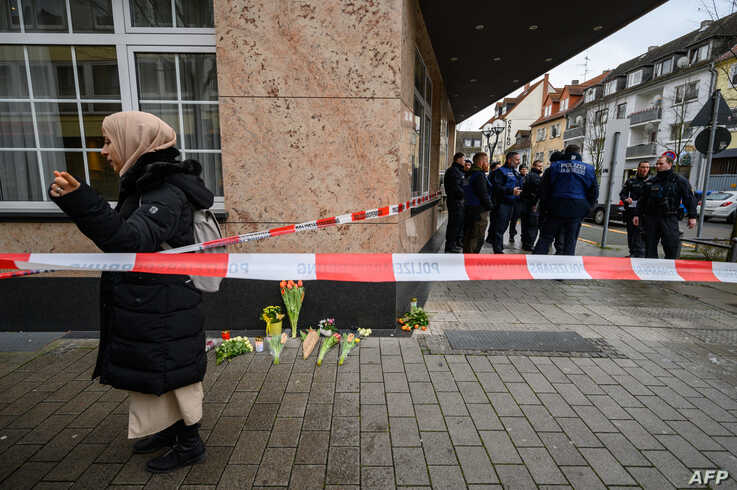 A woman stands beside candles and flowers placed as a tribute to victims of a shooting rampage in Hanau, Germany, Feb. 20, 2020.