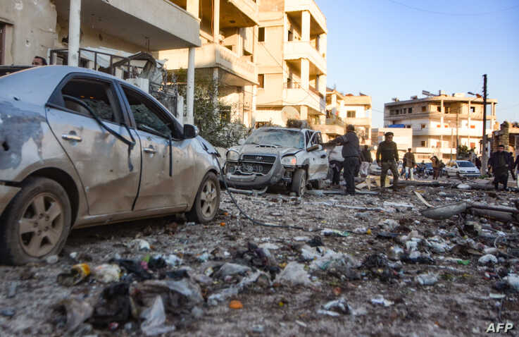 People check damage in a street following an airstrike by Syrian government forces in the town Maarrat Misrin, in Syria's northwestern Idlib province, Feb. 25, 2020.