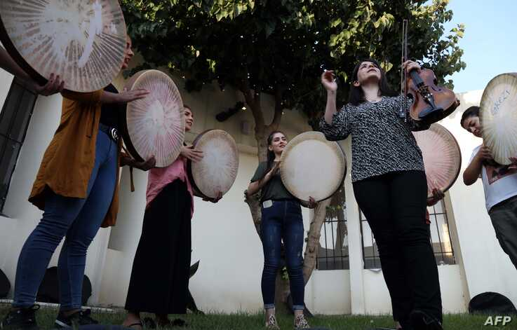 "Young Yazidi and Muslim women, part of the musical group ""40 Plaits,"" rehearse a traditional Kurdish song accompanied by the Daf, a large Kurdish frame drum, in a community center in Dahuk, northwest of the Iraqi capital Baghdad, June 25, 2019."
