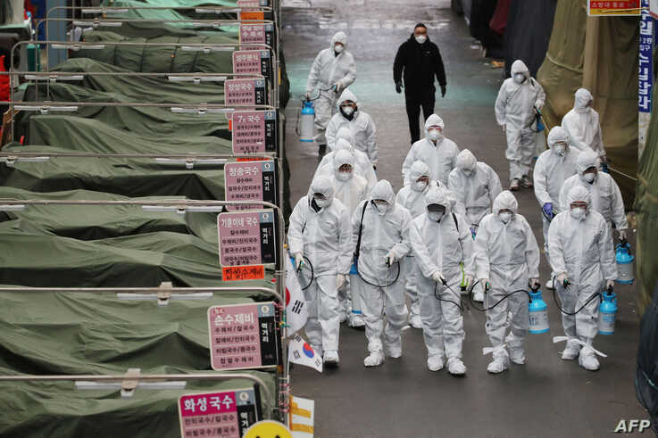 Market workers wearing protective gear spray disinfectant at a market in the southeastern city of Daegu, South Korea, Feb. 23, 2020.