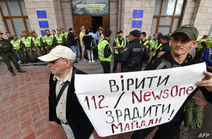 "FILE - Activists protest against TV channels they see as agents of Russian disinformation, in Kyiv, Sept. 5, 2019. Their sign reads ""To believe TV channels '112' and 'NewsOne' is to betray the 'Maidan' (Ukraine's revolution of dignity)."""