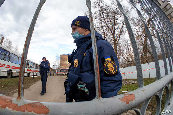 Ukrainian National Guard servicemen patrol by the gate of a military medical facility where evacuees from coronavirus-hit China are quarantined, in the town of Novi Sanzhary, Poltava region, Ukraine, Feb. 21, 2020.