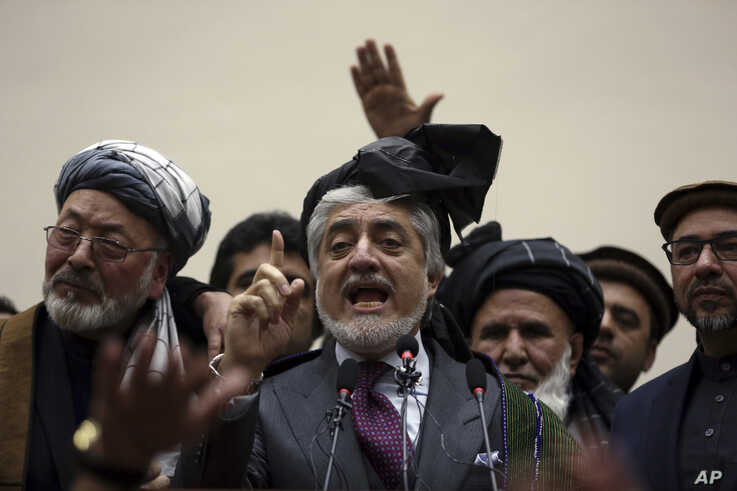 Afghan presidential candidate Abdullah Abdullah, center, addresses the media following a meeting with his party members, in Kabul, Afghanistan, Feb. 18, 2020.