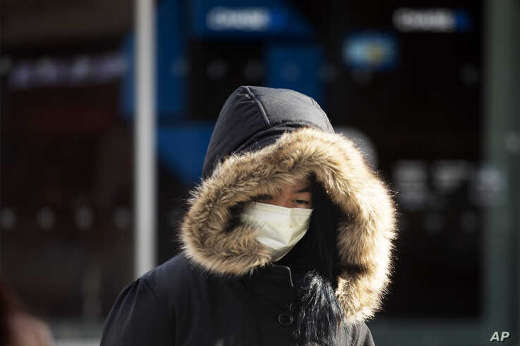 "FILE - A woman, who declined to give her name, wears a mask, in New York City, Jan. 30, 2020. She works in a doctor's office and said she wears the mask ""partly"" out of concern over the coronavirus."