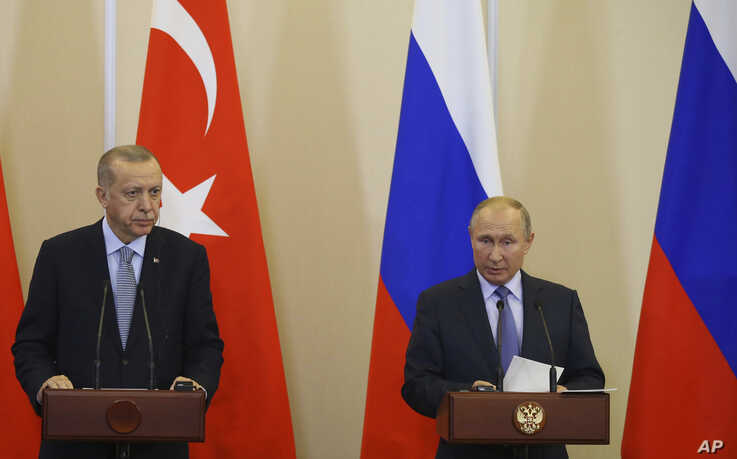 FILE - Turkish President Recep Tayyip Erdogan, left, and Russian President Vladimir Putin are seen during their joint news conference after talks at the Bocharov Ruchei residence in Sochi, Russia, Oct. 22, 2019.