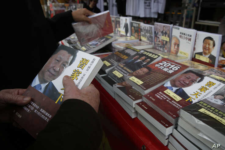 FILE - A customer holds a banned book featuring a photo of Chinese President Xi Jinping on its cover, at a booth at the annual Lunar New Year market in Hong Kong, Feb. 3, 2016.