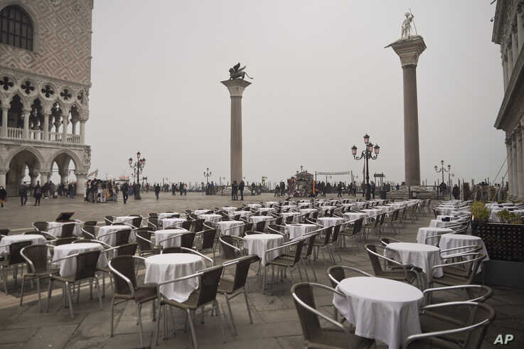 Empty tables sit in St. Mark's square in Venice, Italy. Italy has been scrambling to check the spread of Europe's first major outbreak of coronavirus amid rapidly rising numbers of infections.