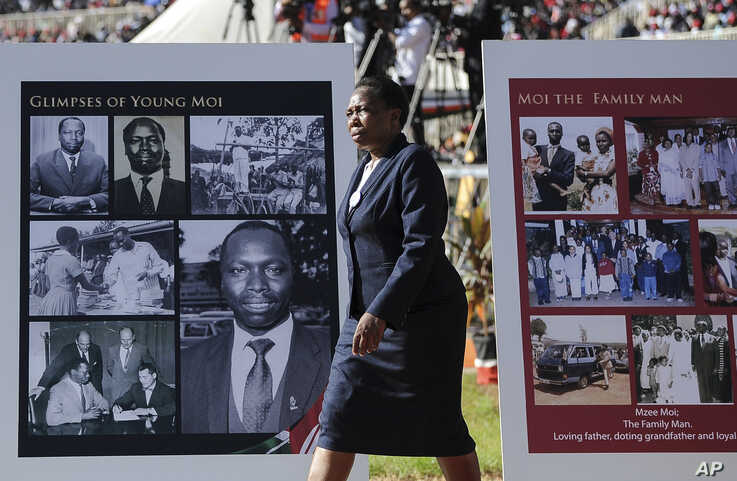A woman walks past memorial placards for former president Daniel arap Moi, at his state funeral in Nyayo Stadium, in Kenya's capital of Nairobi, Kenya, Feb. 11, 2020.