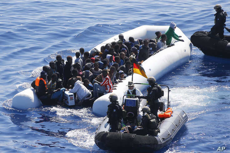 German Navy sailors and Finish Special Forces surround a boat with migrants near the German combat supply ship Frankfurt am Main during the EU's Operation Sophia, in the Mediterranean Sea off the coast of Libya, March 29, 2016.