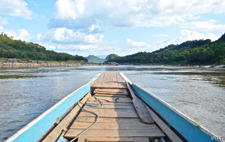 A boat motors down a rocky stretch of the Mekong River in northern Laos in November 2019. (Zsombor Peter/VOA)